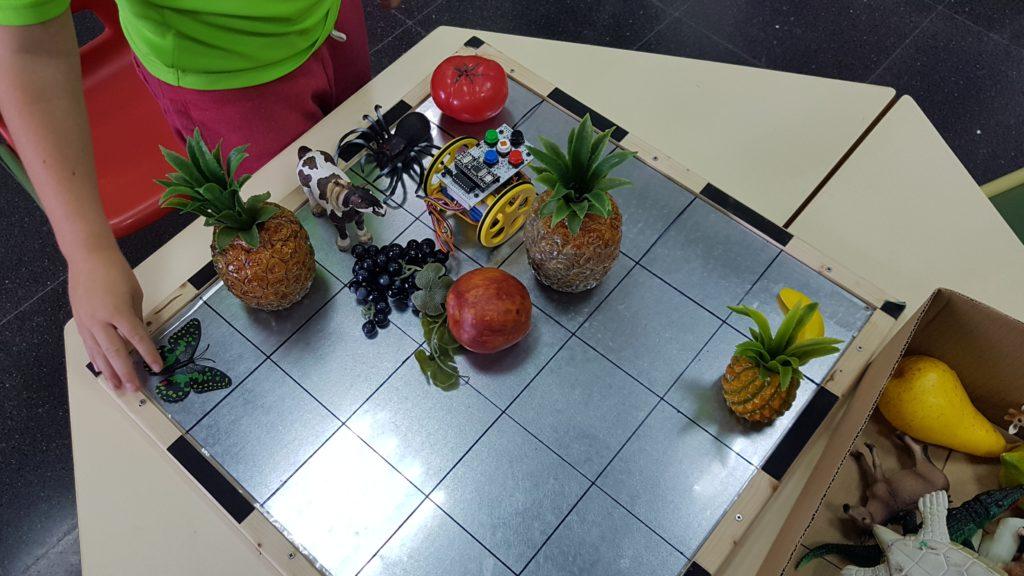 Objetos del tablero: piñas, tomates, plátano y uvas de plástico en tamaño real. Además hay 3 animales: una mariposa de un tamaño próximo al real, una araña y una vaca de tamaño similar y mucho más pequeños que en la realidad.