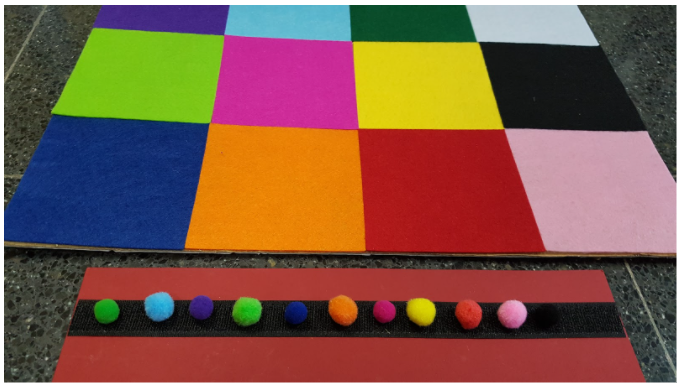 Regleta con 10 pompones de colores que representan la secuencia de celdas que deberá recorrer el robot.