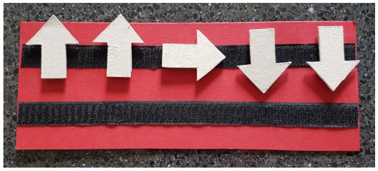 Regleta con velcro sobre la que están adheridas flechas que se corresponden con los movimientos del robot.