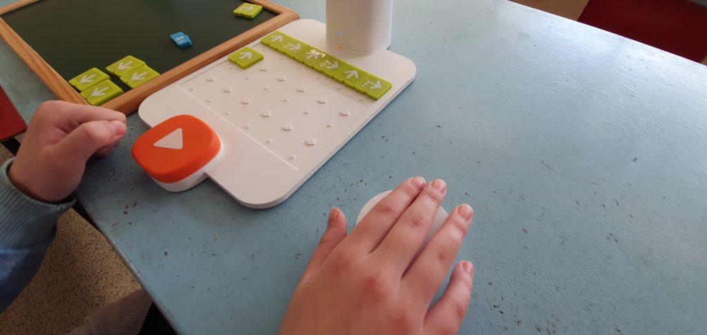 Tablero con tarjetas de movimientos y mano de la alumna sobre el robot