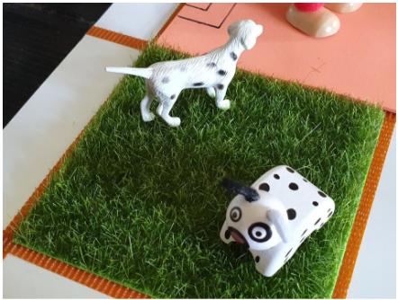 Imagen de dos perros sobre césped artificial. El perro de plástico se parece a uno real, el de madera es más cuadrado.