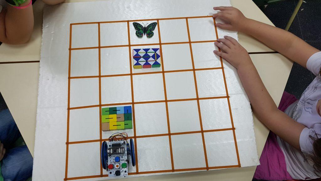 En la imagen se puede ver un robot Escornabot, una mariposa y dos objetos que ocupan dos celdas de un tablero de porexpan de 5x5 celdas