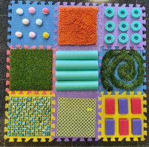 Tablero formado por 9 losetas de gomaeva con los siguientes relieves: pompones grandes, alfombra con gusanos, círculos, césped artificial, ondas de tubo de piscina, espiral de guirnalda, piedras, entramado de plástico y esponjas
