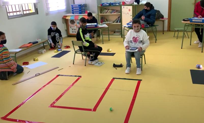 Circuito marcado con cinta aislante roja en el suelo. Una alumna, con su tablet, comprueba que el robot sigue correctamente el circuito.