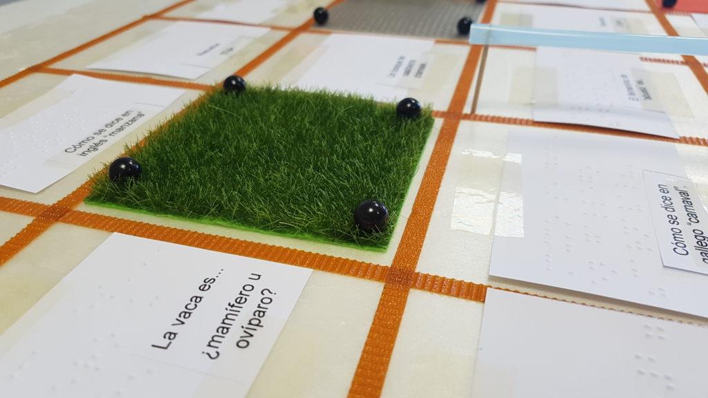 Tablero de porexpan con tarjetas de preguntas en braille y tinta, adheridas con cinta adhesiva, y un trozo de césped artificial, fijado con pequeñas chinchetas en sus esquinas.